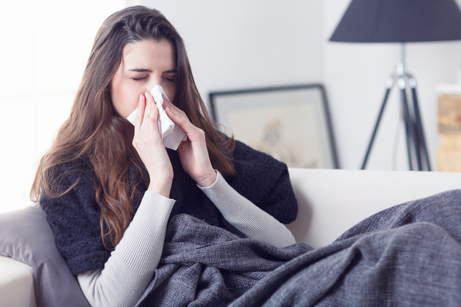 Young attractive woman lying sick at home couch in cold and flu sneezing nose with tissue covering with blanket