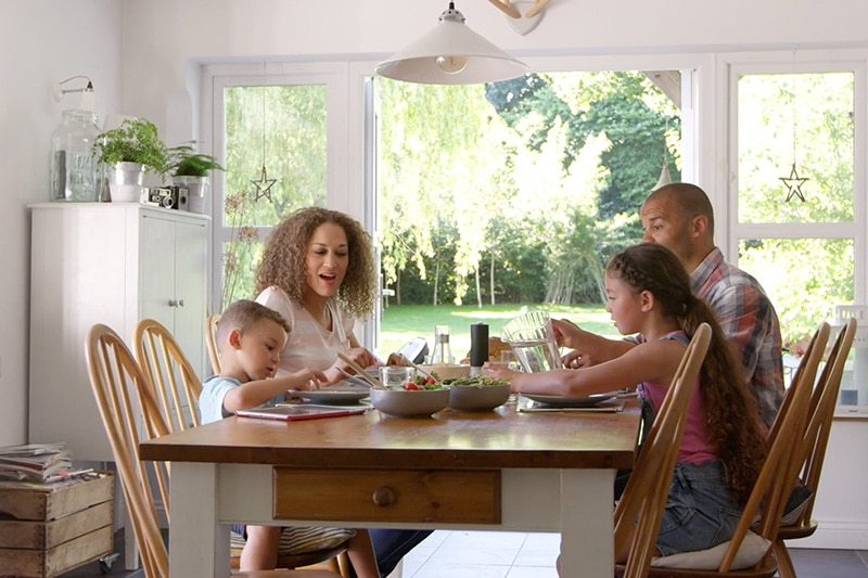 Indoor Air Quality Affects Your Family's Health, family of four sharing a meal in naturally lit home dining room