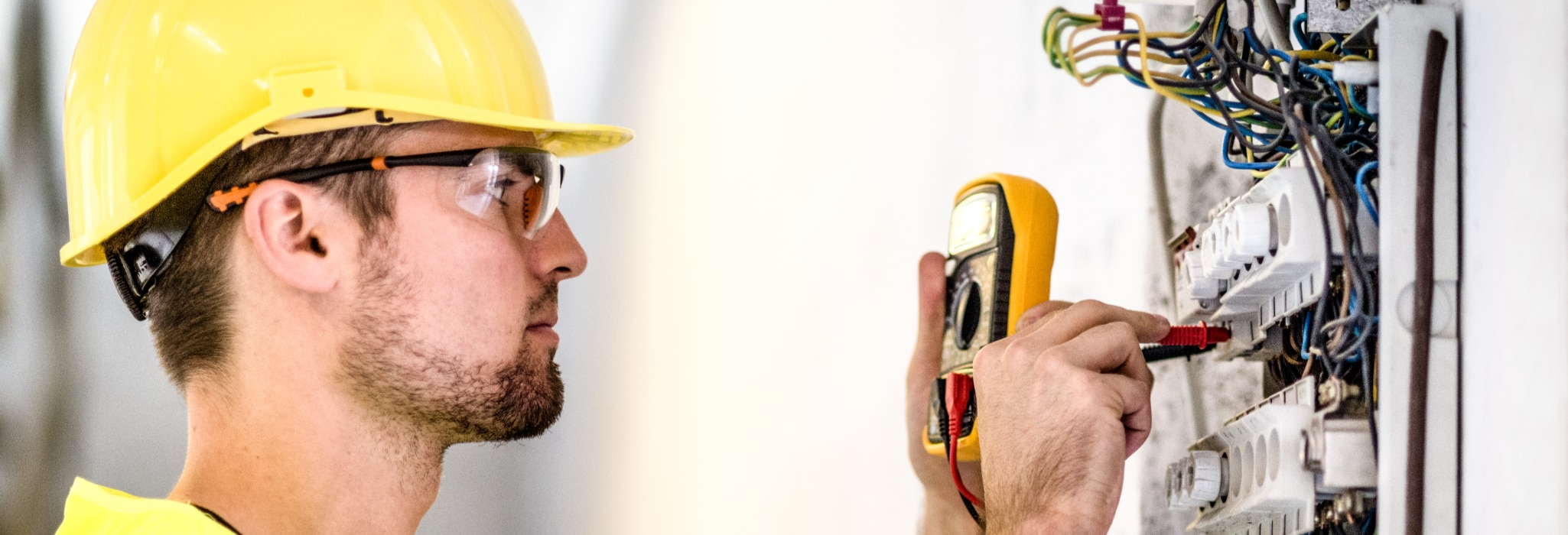 Electrician repairing circuit breakers in industrial electric panel.